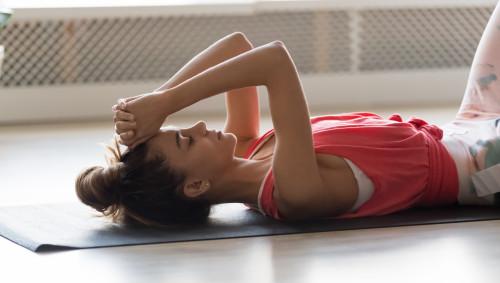 Eine Frau liegt auf einer Fitnessmatte, sie ist erschöpft vom Workout.