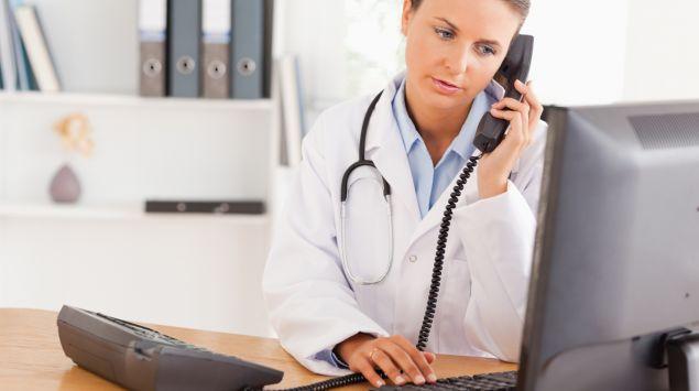 Eine Ärztin sitzt am Schreibtisch und telefoniert.