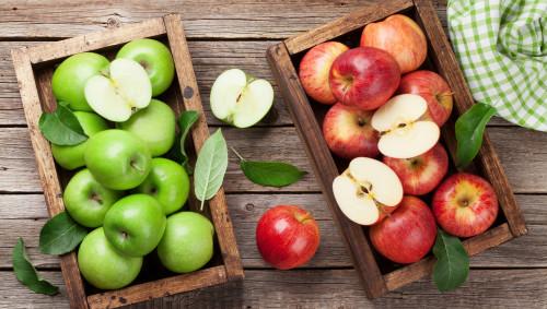 Auf einem Holztisch stehen zwei Holzkisten mit roten und grünen Äpfeln.