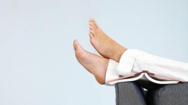 Das Bild zeigt eine Person, die die Füße auf einer Sofalehne hochlegt.