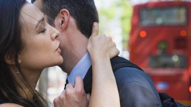Eine Frau küsst einen Mann, im hintergrund sieht man einen roten Doppeldecker-Bus.