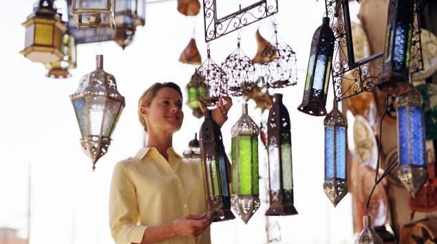 Eine Frau steht in einem orientalischen Lampenladen.