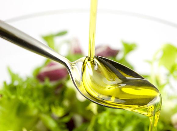 Bluthochdruck senken: Olivenöl fließt auf einen Esslöffel, im Hintergrund sieht man grünen Salat.