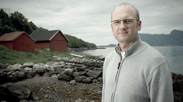 Ein Mann steht an einem See vor zwei Holzhäuschen.