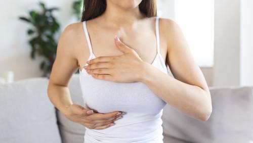 Eine Frau tastet ihre Brüste ab.