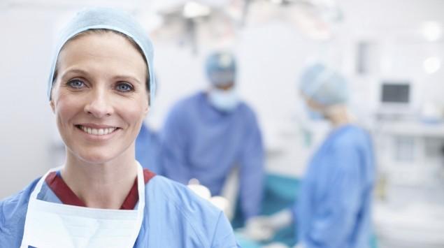 Eine lächelnde Ärztin steht im OP-Saal, im Hintergrund führen Kollegen einen Eingriff durch.