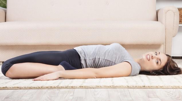 Eine Frau dehnt ihr Muskeln auf dem Fußboden vor einem Sofa.
