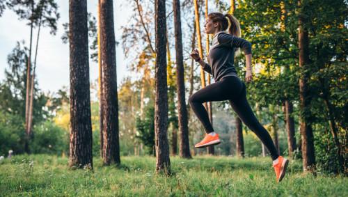 Eine Frau joggt (läuft) im Wald.