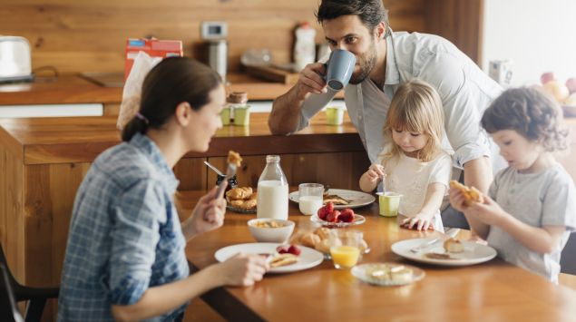 Eine junge Frau, ein Mädchen und ein Junge sitzen am Tisch und frühstücken; hinter dem Mädchen steht ein junger Mann und trinkt aus einer Tasse.