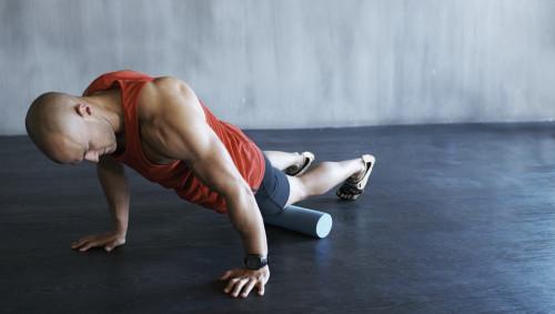 Das Bild zeigt einen sportlichen Mann, der mit einer Faszienrolle seine Oberschenkelvorderseite trainiert.