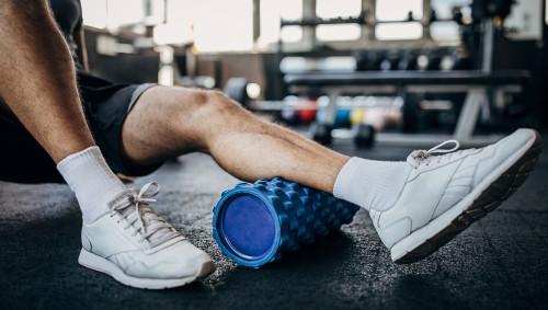 Ein Mann trainiert seine Beine mit einer Faszienrolle.