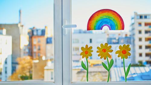 Ein aufgeklebter Regenbogen und Blumen auf einer Fensterscheibe.