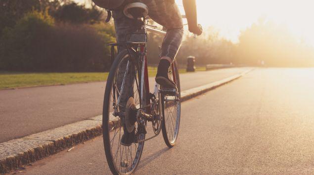 Eine junge Frau fährt mit dem Rad auf einer Straße.