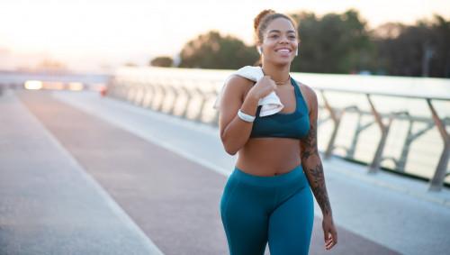 Eine Frau in türkisem Sportoutfit und Handtuch läuft lächelnd.