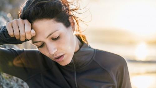 Eine Frau ist verschwitzt vom Sport und wischt sich mit der Hand über die Stirn.