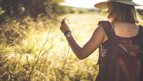Das Bild zeigt eine junge Frau mit Rucksack, die durch hohes Gras wandert.
