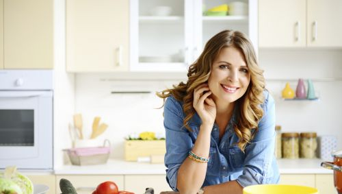 Eine Frau stützt sich in der Küche auf die Arbeitstheke.