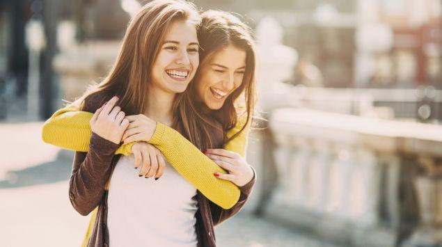 Eine junge Frau legt ihre Arme von hinten um eine andere junge Frau; beide lachen.