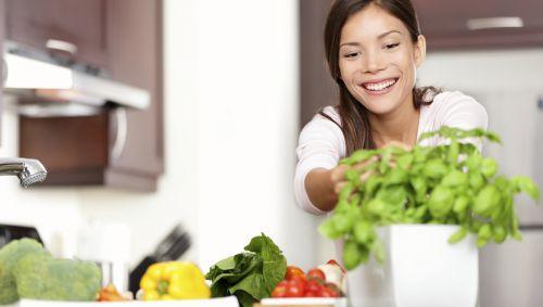 Eine junge Frau bereitet in der Küche Essen mit verschiedenen Gemüsesorten und frischen Kräutern zu.