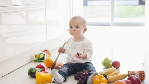 Ein Baby sitzt inmitten von viel Gemüse.