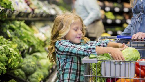 Das Bild zeigt ein junges Mädchen, das einen Salatkopf in einen Einkaufswagen legt.
