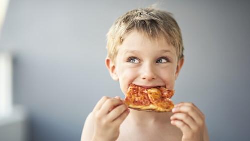 Ein kleiner Junge isst Pizza.