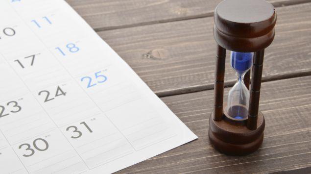 Man sieht ein Kalenderblatt und eine Sanduhr.