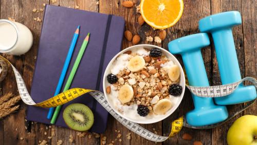 Gesundes Frühstück, Gewichte und ein Notizbuch.