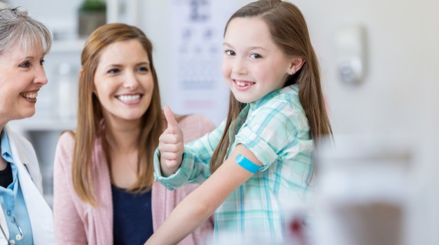 """Man sieht ein Kind mit seiner Mutter beim Arzt. Das Kind signalisiert """"Daumen hoch""""."""