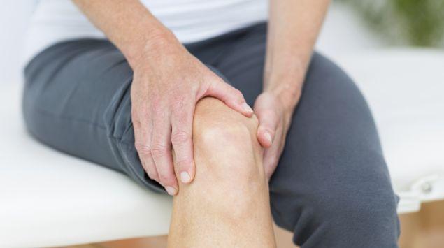 Das Bild zeigt eine Frau, die ihr Knie abtastet.