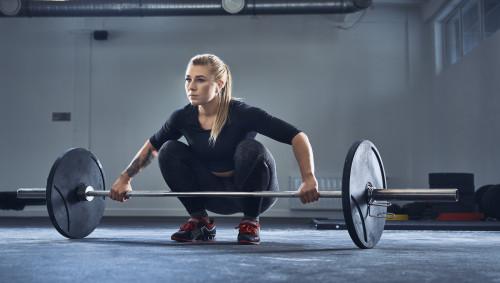 Eine Frau im Fitnessstudio mit einer Langhantel.