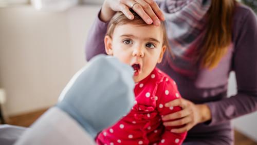 Ein Kleinkind wird mit Tupfer auf Corona getestet