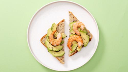 Eine Scheibe Toastbrot mit Avocado und Shrimps auf einem weißen Teller mit grünem Hintergrund.