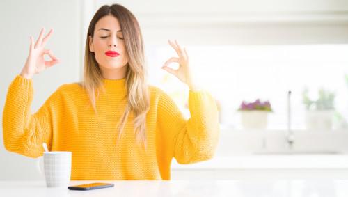 Eine Frau meditiert mit ihrem Smartphone