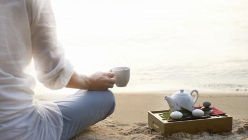 Eine Frau sitzt am Strand und hält eine Tasse in der Hand, neben ihr ein Tablett mit einer Teekanne.