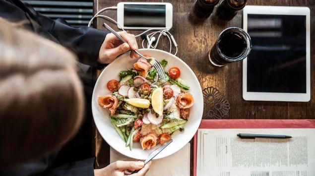 Das Bild zeigt eine Geschäftsfrau beim Mittagessen.