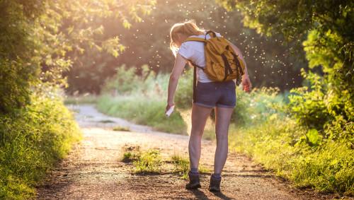 Eine Frau in kurzer Hose sprüht sich auf einem Wanderweg an einem Sommertag die Beine ein