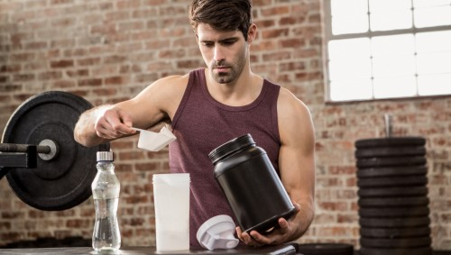 Ein Mann mixt sich ein Proteinshake.