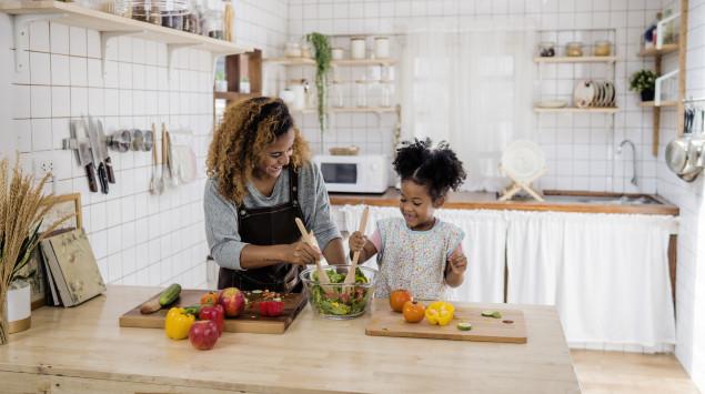 Eine Mutter kocht mit ihrer Tochter gesundes Essen.