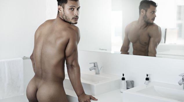 Ein nackter Mann steht vor einem Spiegel.