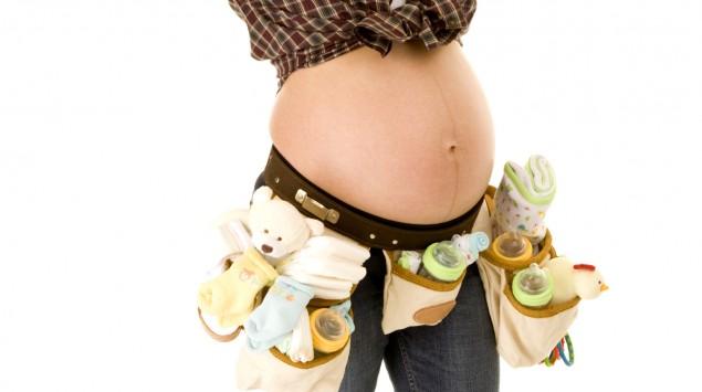 Eine Schwangere mit Werkzeuggürtel und Schutzhelm.
