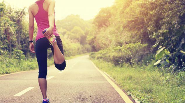 Das Bild zeigt eine Joggerin, die Ihren Oberschenkel dehnt.