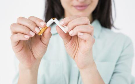Bluthochdruck senken: Eine Frau zerbricht eine Zigarette.