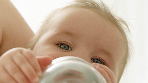 Ein Säugling trinkt Wasser aus einer Flasche.