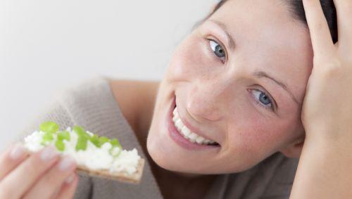 Das Bild zeigt eine junge Frau, die eine Scheibe Knäckebrot isst.