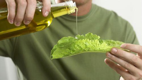 Das Bild zeigt einen Mann, der Öl auf ein Salatblatt gießt.