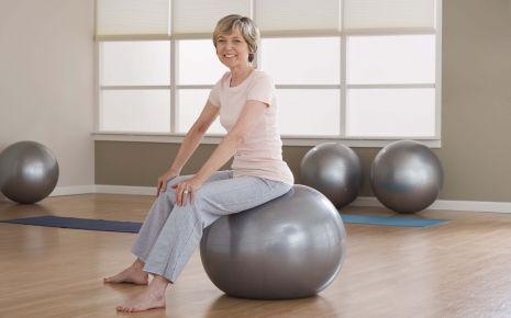 EIne ältere Frau sitzt aufrecht auf einem Gymnastikball.