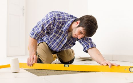 Schleimbeutelentzündung: Ein Mann arbeitet beim Fliesenlegen mit einer Wasserwaaage auf dem Boden.