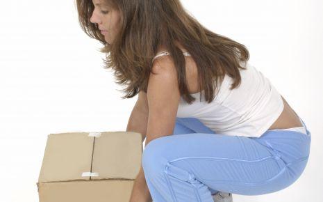 Das Bild zeigt eine Frau, die ein Paket anhebt.