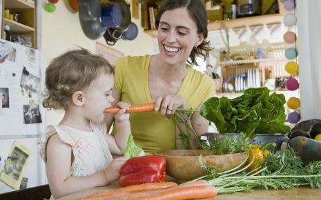 Eine Mutter bereitet mit ihrem Kind Essen zu.